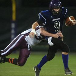John Bapst's Spencer Baron (right) is tackled by Maine Central Institute Mitchell Hallee during their football game at Husson University in this September 2014 file photo. John Bapst and Orono face off at 7 p.m. Friday at the University of Maine in Orono.