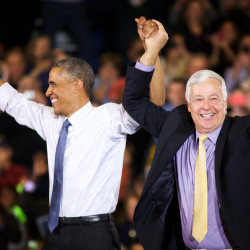 President Barack Obama raises Democratic gubernatorial candidate Mike Michaud's hand at a rally in Portland on Thursday night.